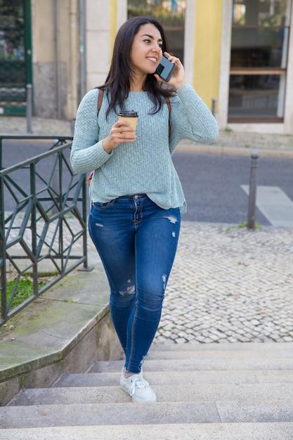 電話で話していると街の階段を歩いて笑顔の女性 無料写真