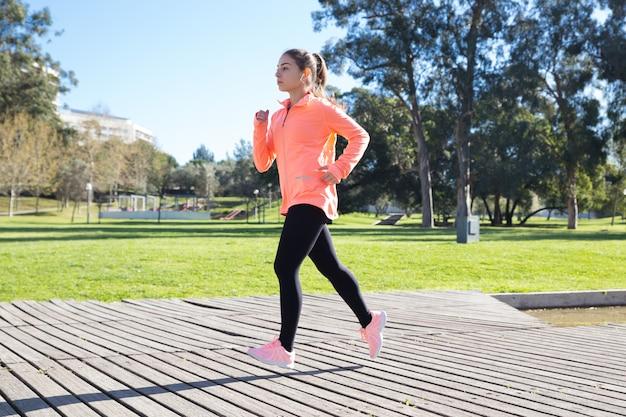 都市公園でジョギングする若い魅力的な女性 無料写真