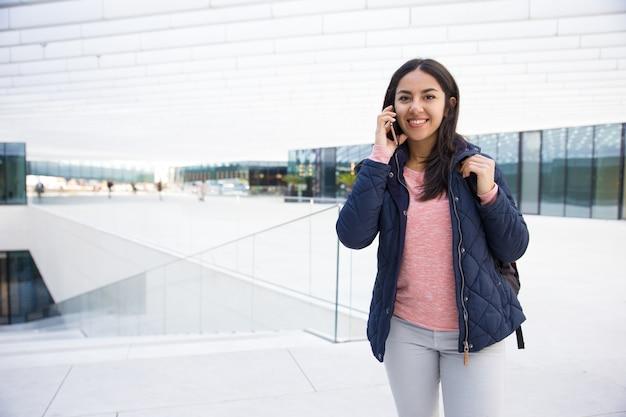 携帯電話で話している陽気なインド人学生の女の子 無料写真