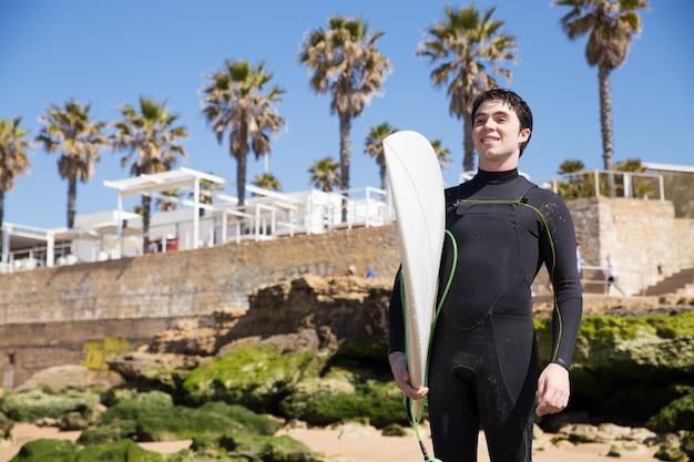 太陽が降り注ぐビーチでサーフボードを持って幸せなハンサムな若い男 無料写真