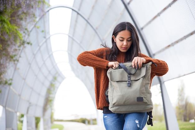 深刻な若い女性が屋外のバッグに電話を見つける 無料写真