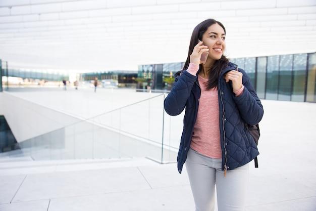 屋外での携帯電話を使用して、ランドセルとかわいい女の子を笑顔 無料写真