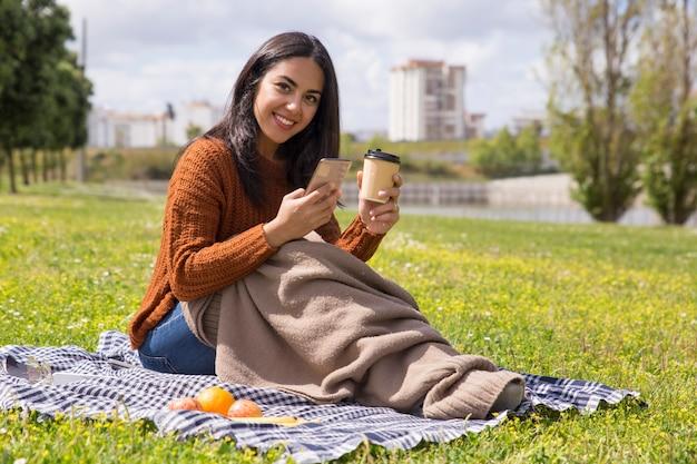 コーヒーを飲みながら格子縞に包まれた笑顔の学生少女 無料写真