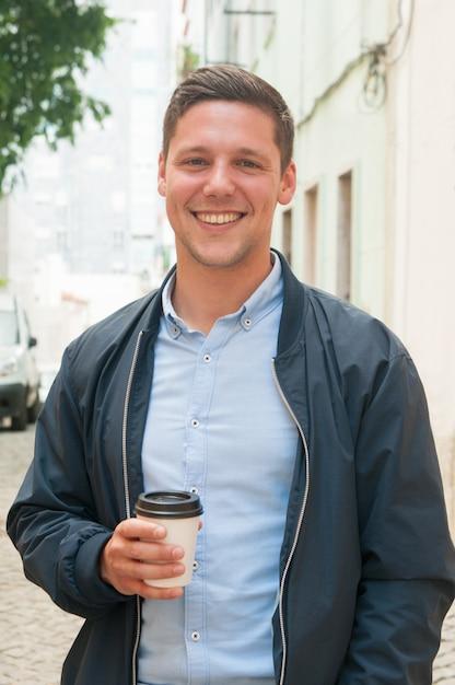 屋外のコーヒーブレークを楽しんでいる陽気な男 無料写真