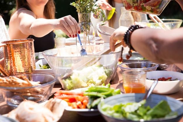 ボウルと皿を食べ物と女性の手でフォークのクローズアップ 無料写真