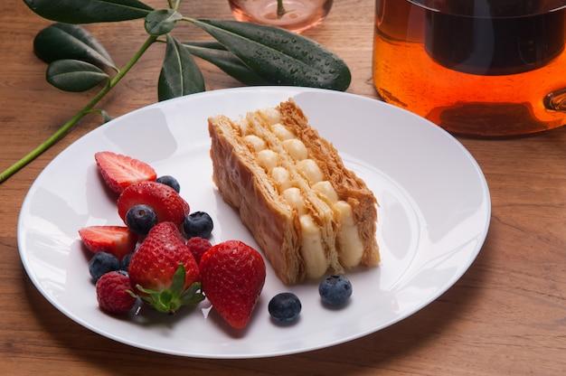 ナポレオンケーキ部分と皿の上の新鮮な果実のクローズアップ 無料写真