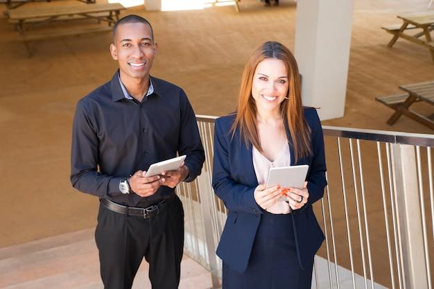 同僚のポーズとタブレットコンピューターを階段の上に保持 無料写真