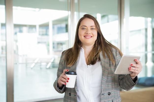 タブレットとコーヒーを屋外で保持している幸せなビジネス女性 無料写真