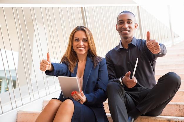 タブレットを押しながら階段に親指を現して幸せな同僚 無料写真