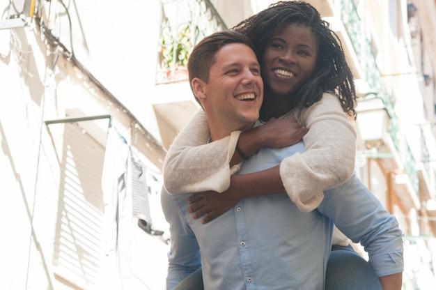 屋外の背中にガールフレンドを運ぶ幸せな若い男 無料写真