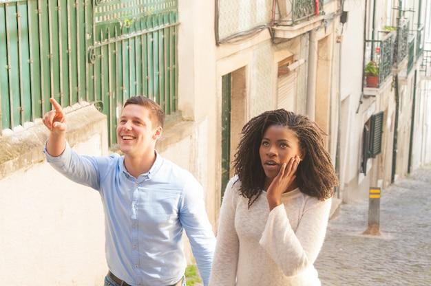 ランドマークで興奮している観光客の異人種間のカップル 無料写真