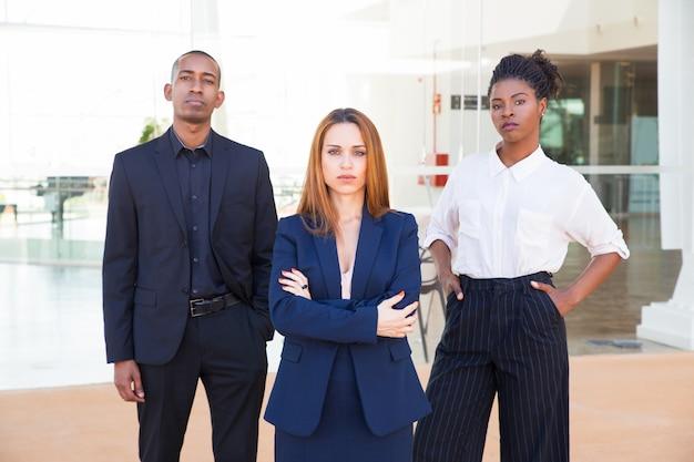 女性ビジネスリーダーとカメラ目線の彼女のチーム 無料写真