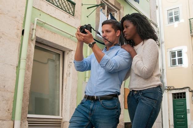 通りでカメラに写真を撮る肯定的な魅力的なカップル 無料写真