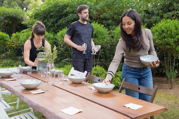 Позитивные люди подают на стол с тарелками на открытом воздухе Бесплатные Фотографии