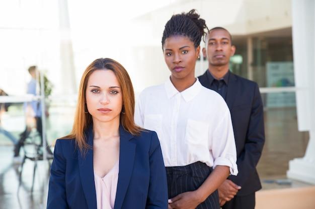 Серьезные уверенные деловые люди, стоящие в ряду Бесплатные Фотографии