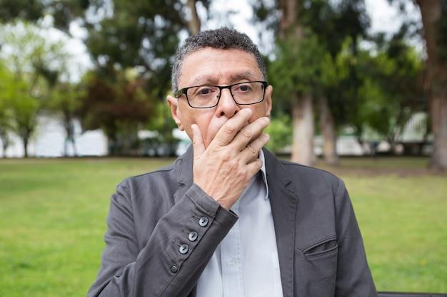 公園で手で口を覆っているショックを受けた中年の男 無料写真