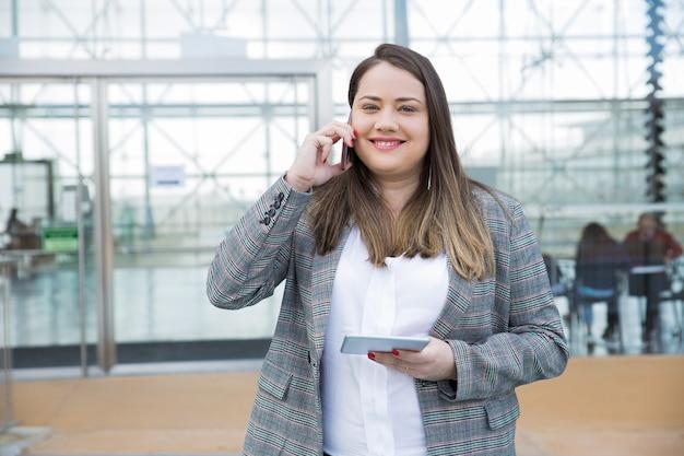 スマートフォンを屋外で呼び出すビジネス女性の笑みを浮かべてください。 無料写真