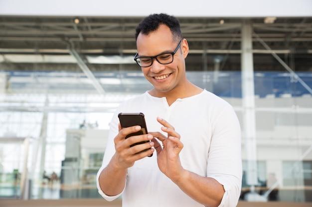 スマートフォン屋外で若い男のテキストメッセージを笑顔 無料写真