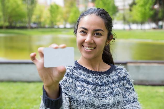 都市公園における空白の名刺を示す若い女性の笑みを浮かべてください。 無料写真