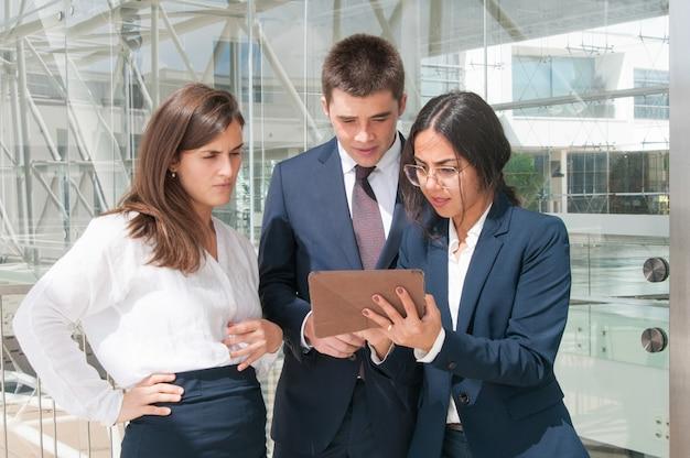 タブレット、集中的に探している同僚のデータを示す女性 無料写真