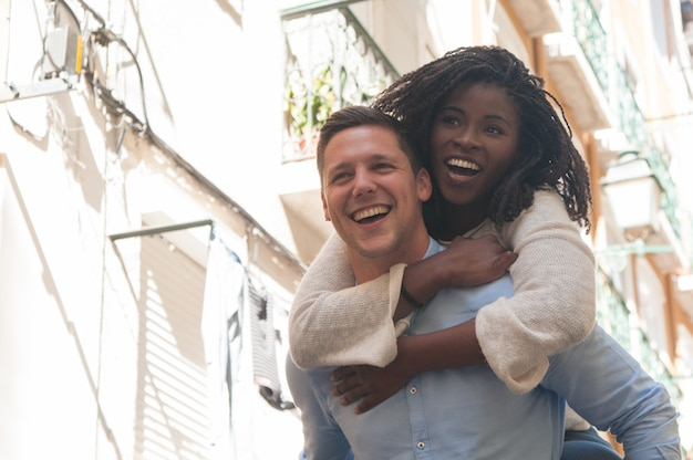 笑いと屋外の背中にガールフレンドを運ぶ若い男 無料写真