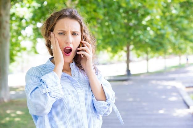 非常にショックを受けた少女は電話の話に腹を立てた 無料写真