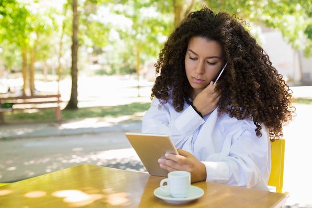 電話で呼び出して、屋外カフェでタブレットを使用して焦点を当てた女性 無料写真