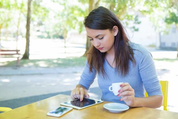コーヒーを飲みながら、屋外カフェでタブレットを使用して女性に焦点を当ててください。 無料写真