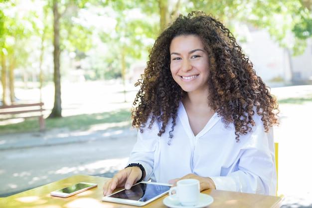 公園のカフェテーブルでタブレットコンピューターで閲覧して幸せな女性 無料写真