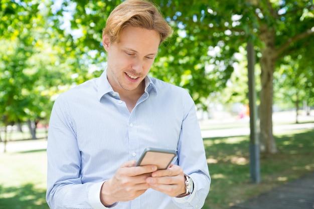 電話で物思いに沈んだ笑みを浮かべて男テキストメッセージ 無料写真