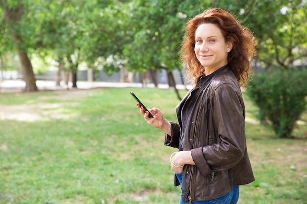 都市公園でスマートフォンを使用して肯定的な若い女性 無料写真