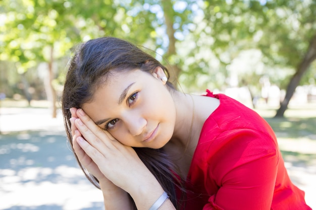 リラックスして公園でカメラにポーズ穏やかなかなり若い女性 無料写真