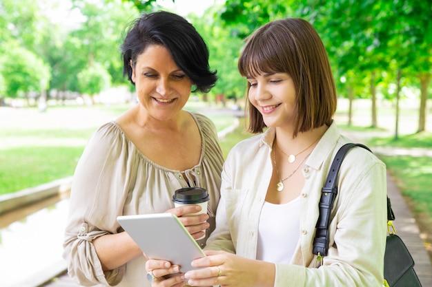 Улыбается молодая женщина и ее мать, с помощью планшета в парке Бесплатные Фотографии
