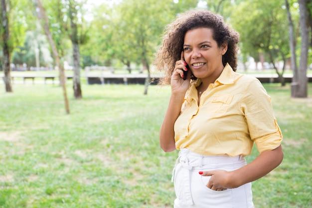 都市公園で電話で話している若い女性の笑みを浮かべてください。 無料写真