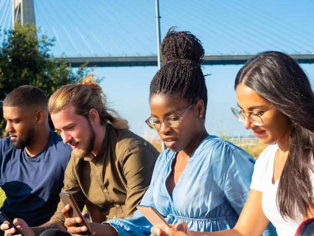 屋外で携帯電話を使用して集中している友人 無料写真