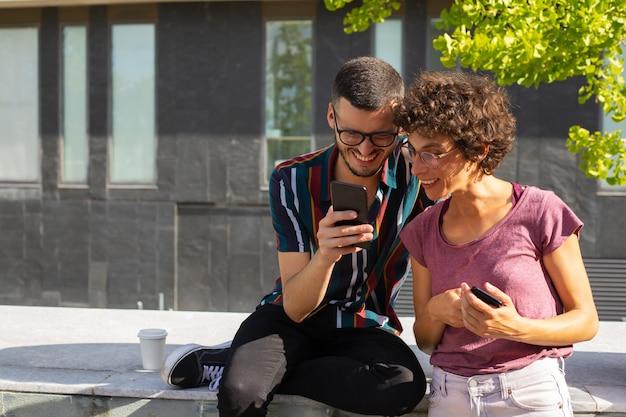 電話で面白いコンテンツを見て幸せなオタクカップル 無料写真