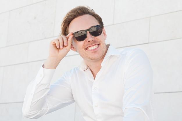 Улыбаясь деловой человек, регулируя солнцезащитные очки на открытом воздухе Бесплатные Фотографии