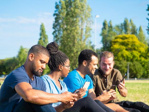 公園でスマートフォンを使用して友達に笑顔 無料写真