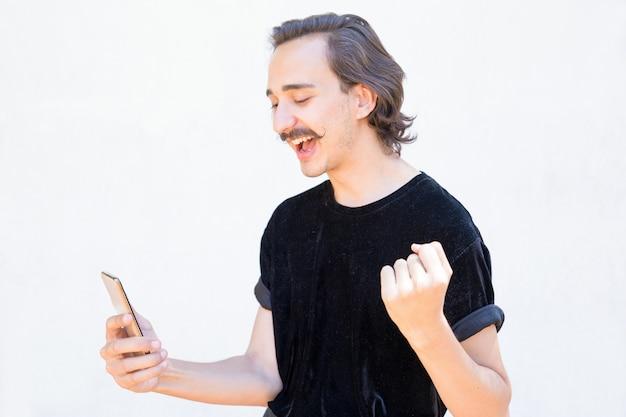 電話を使用してハンドルの口ひげを持つ成功した若い男。 無料写真