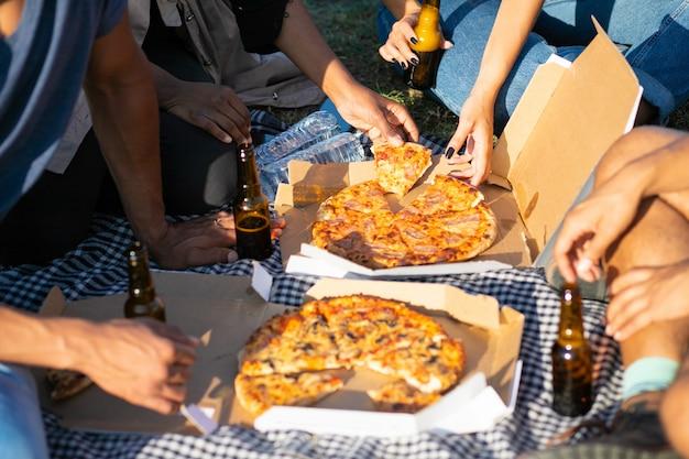 Обрезанное выстрел из друзей, пикник в парке летом. молодые люди сидят на лугу с пиццей и пивом. концепция пикника Бесплатные Фотографии
