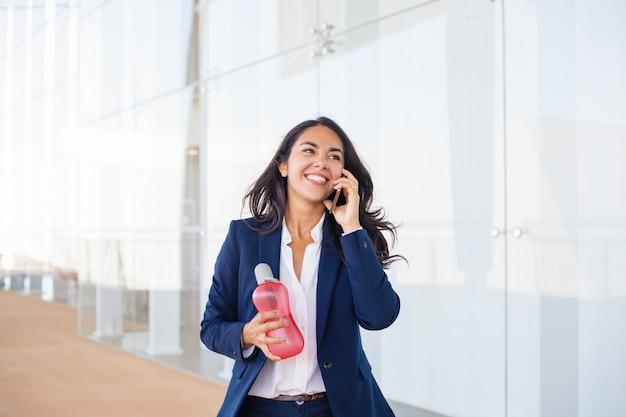 Счастливая молодая женщина разговаривает по мобильному телефону Бесплатные Фотографии