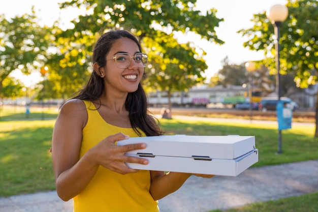 Счастливая латинская женщина курьер, перевозящих пиццу в парке Бесплатные Фотографии