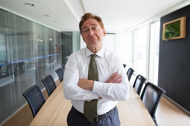 会議の中に立つ懐疑的な上司のビジネスマン 無料写真