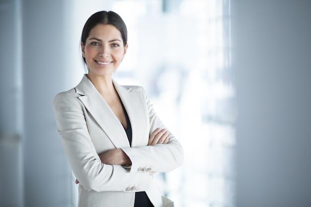 Улыбаясь женщина бизнес-лидера с оружием, пересекли Бесплатные Фотографии