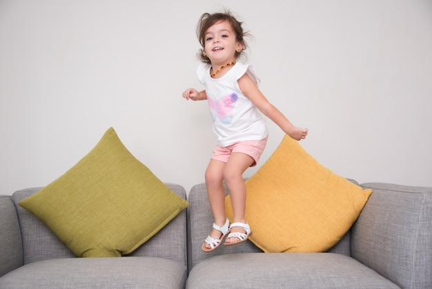 優雅な女の子、ソファーで飛び降りる 無料写真