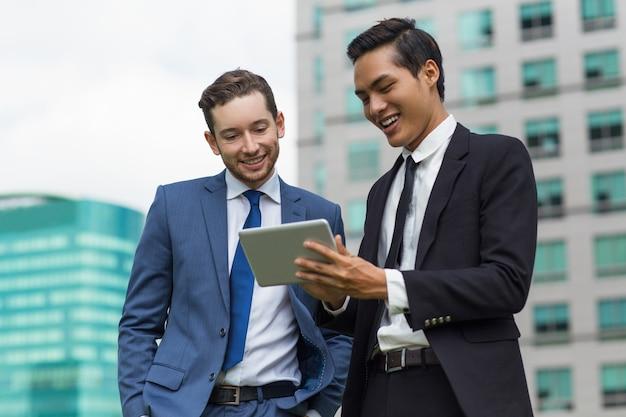 屋外でタブレットを使用して笑顔の同僚のクローズアップ 無料写真