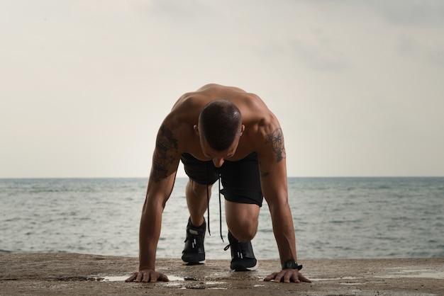 地面にプッシュアップをしている大きな筋肉の男 無料写真