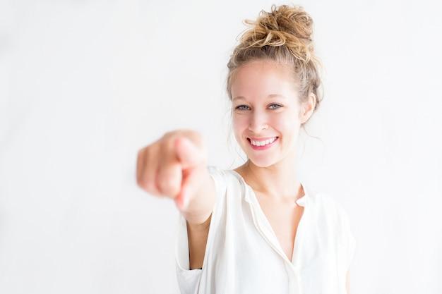 Улыбаясь молодая симпатичная женщина указывая на вас Бесплатные Фотографии