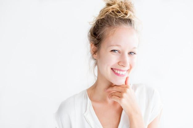 Улыбаясь молодая симпатичная женщина, касаясь подбородка Бесплатные Фотографии