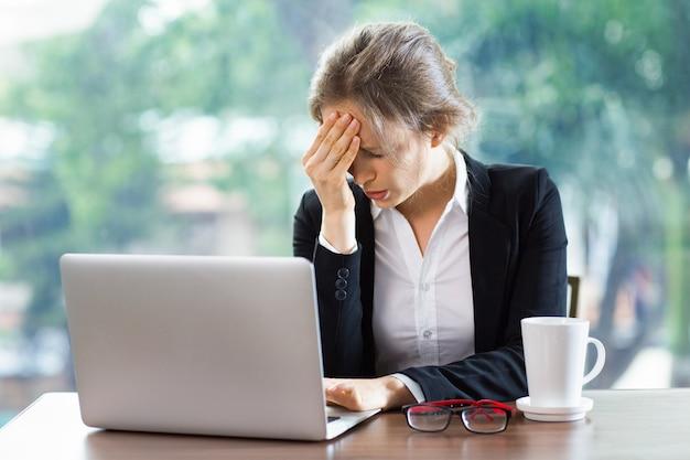 ノートパソコンとコーヒーとの強い頭痛を持つ女性 無料写真